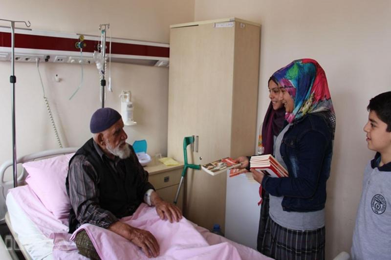 Öğrenciler hastanede hastalarla birlikte kitap okuyor
